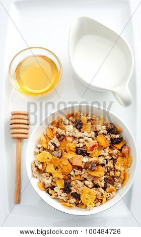 Healthy nutritious bowl of cereal with honey and milk