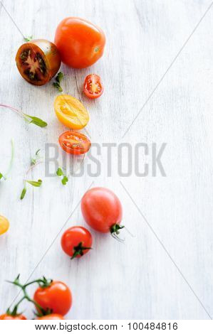 Still life arrangement of cut and whole cherry, roma, green, yellow tomatoes on rustic background with copy space