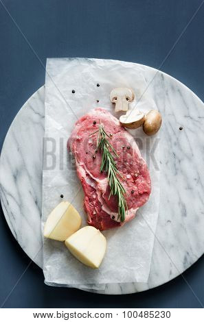 Piece of raw beef steak with potatoes and mushroom, overhead on dark background