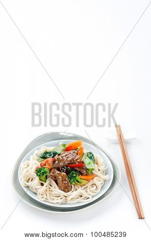 Beef stir-fry with broccoli and other vegetables on oriental noodles, plenty of copy space