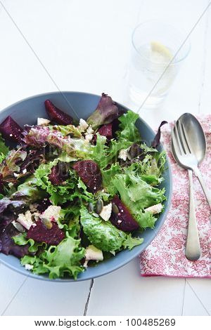 Bowl of salad with rocket, feta, beetroot and seeds  with glass of water and spoon and fork