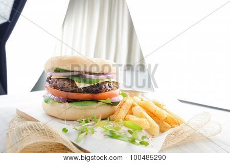 Food photography of classic cheeseburger with photographic lighting in background
