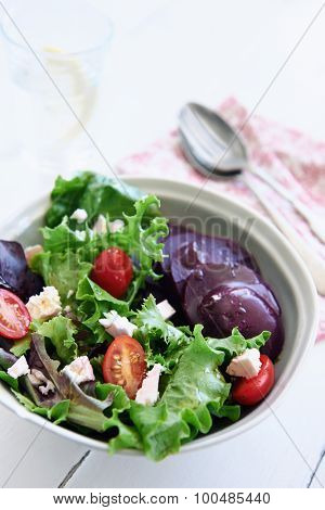 Bowl of salad with rocket, goat's cheese, beetroot, tomatoes and seeds  with glass of water and spoon
