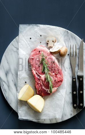 Overhead of raw meat with cutlery, dinner preparation on marble