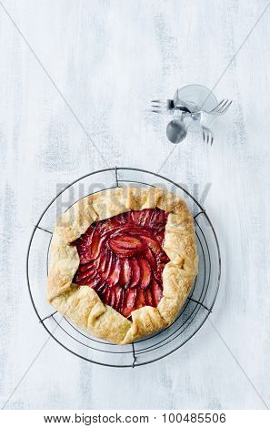 Whole plum galette, a french dessert pie tart with sweet homemade crust overhead with serving cutlery