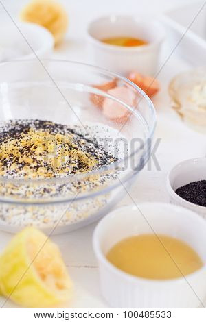 Bowl with mixture of poppy seeds, flour, and lemon zest with egg and lemon ingredients next to it