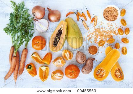 Overhead horizontal of fresh orange toned vegetables and fruit raw produce on white rustic background, pumpkin butternut carrot papaya pawpaw capsicum pepper sweet potato cherry tomatoes chilli orange