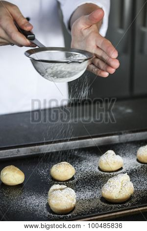 Powdering cream puffs in the kitchen