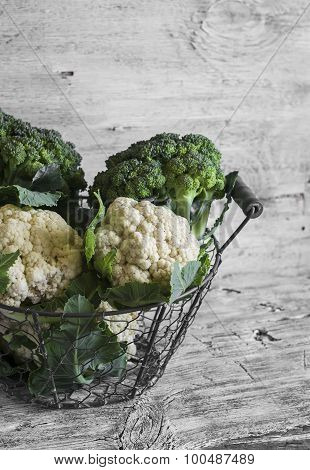 Fresh Cauliflower And Broccoli In A Vintage Metal Basket On A Light Wooden Surface