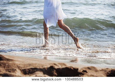 barefoot woman in white shirt run through sea water on sandy beach, side view