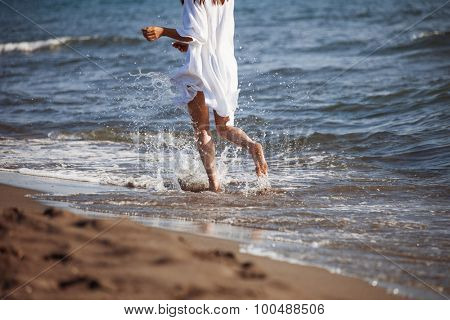 barefoot woman in white shirt run through sea water on sandy beach, back view, lower body