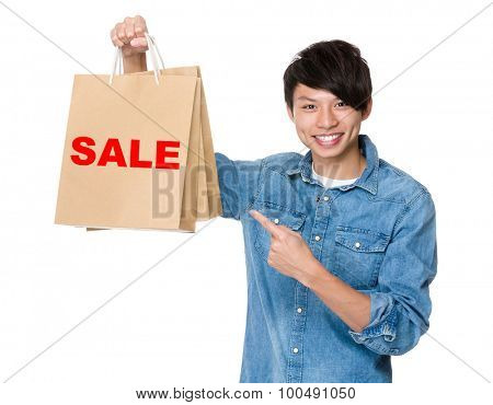 Man finger point to shopping bag for showing a word of sale