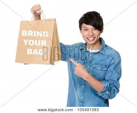 Man finger point to shopping bag for showing phrase of bring your bag