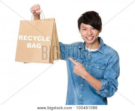 Man finger point to shopping bag for showing phrase of recycyle bag
