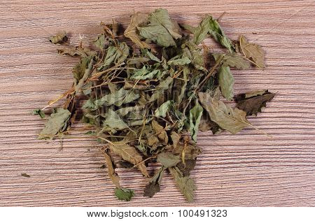 Heap Of Dried Lemon Balm On Wooden Surface