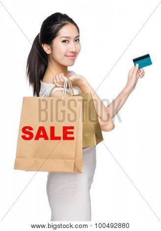 Woman with credit card and holding shopping bag for showing a word sale