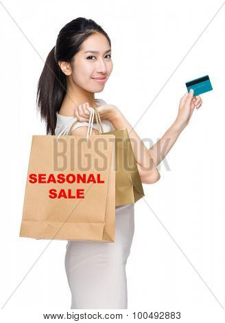 Woman with credit card and holding shopping bag for showing seasonal sale