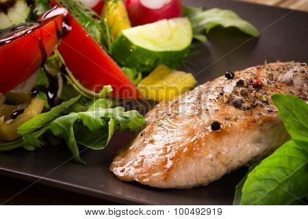 Roasted chicken breast with spices and fresh vegetables on wooden background