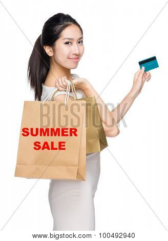 Woman with credit card and holding shopping bag for showing summer sale
