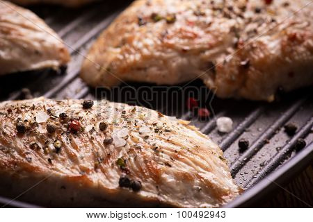 Chicken breast with spices on iron pan grill, closeup view