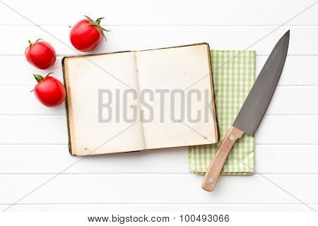 cookbook and tomatoes on kitchen table