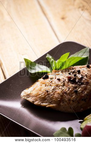 Roasted chicken breast with spices and basil on wooden background