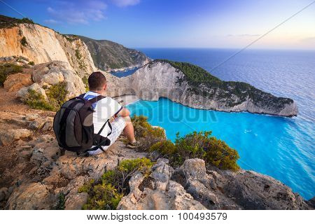Man with backpack sitting watching sunset over Navagio beach on Zakynthos island, Greece