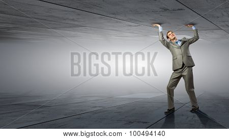 Businessman under pressure between two stone walls