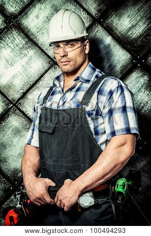 Handsome costruction worker wearing uniform and tools over grunge industrial background. Job, occupation.