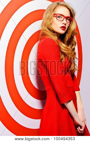 Gorgeous fashion model in red dress and elegant red glasses posing over red circles of the target. Beauty, fashion. Optics, eyewear.