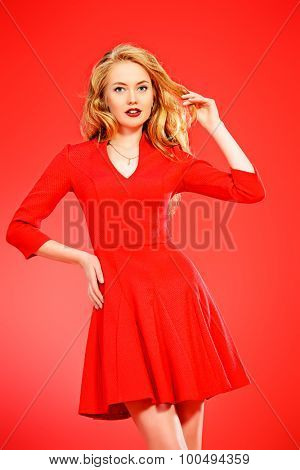 Charming smiling young woman in red dress and with blonde curled hair. Beauty, fashion. Cosmetics, make-up. Red background.