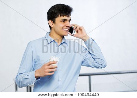 Young man with coffee in hand talking on mobile phone