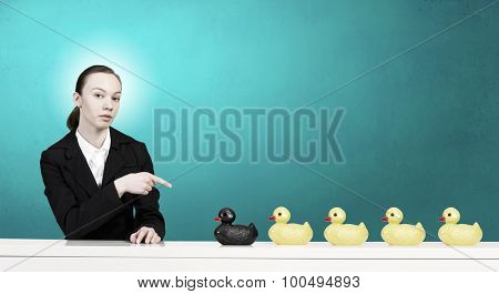 Young businesswoman pointing with finger at yellow rubber duck toy on table
