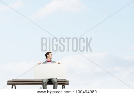 Young man sitting on bench with white banner