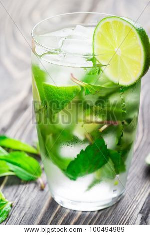 Mojito cocktail with lime on a rustic wooden background