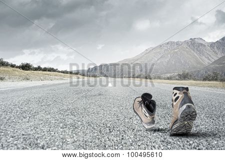 Pair of hikers boots walking on road