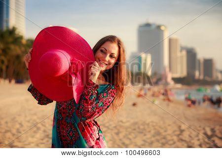Slim Girl Holds Big Hat Behind Back On Beach Near City Sea