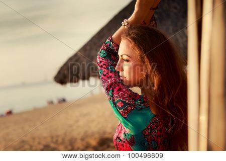 Slim Girl In Colorful By Reed Wall Against Defocused Background
