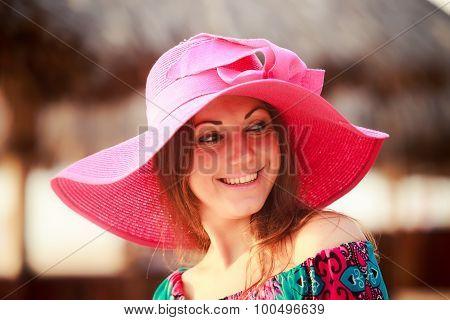 Brunette Girl In Big Red Hat Smiles Winks At Defocused Umbrella