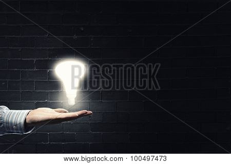 Close up of hand holding light bulb in palm