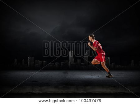 Running man in red sport wear on dark background