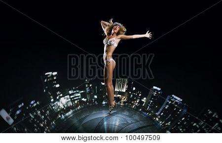 Hot young dancing woman in white bikini on night city background