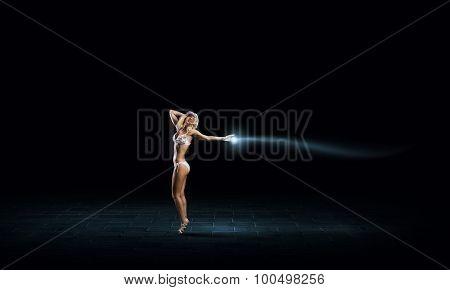 Hot young dancing woman in white bikini on dark background