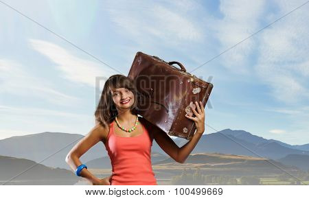 Young retro woman with her vintage baggage on shoulder