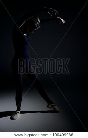Ballerina Exercising In The Darkness
