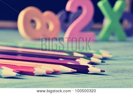closeup of a pile of pencil crayons of different colors and some numbers on a blue rustic wooden table in a classroom, with a filter effect
