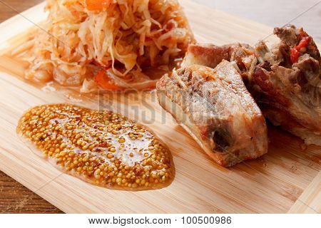 Roasted Pork Ribs With Tomato, Carrots And Cabbage On A  Cutting Board