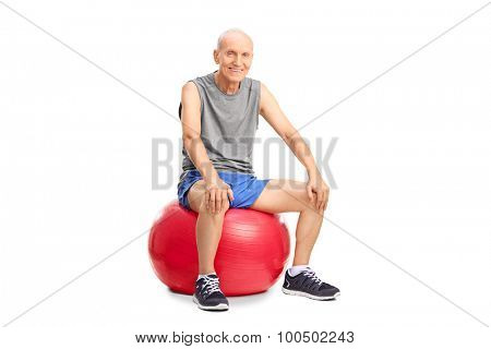 Cheerful senior man in sportswear sitting on a red fitness ball and looking at the camera isolated on white background