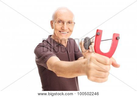 Cheerful senior man shooting a slingshot and looking at the camera isolated on white background
