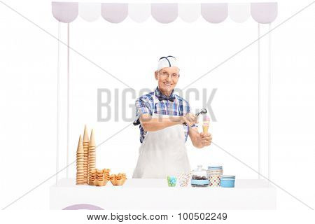 Mature ice cream seller making an ice cream behind a stall and looking at the camera isolated on white background